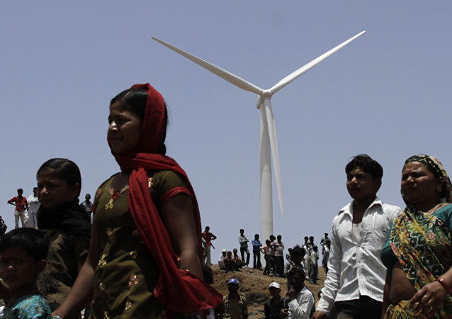Indian villagers walk past a wind mill during the inauguration of ReNew Power's 25.2 MW wind farm near Jasdan town, about 200 kilometers (125 miles) from Ahmadabad, India. (File)