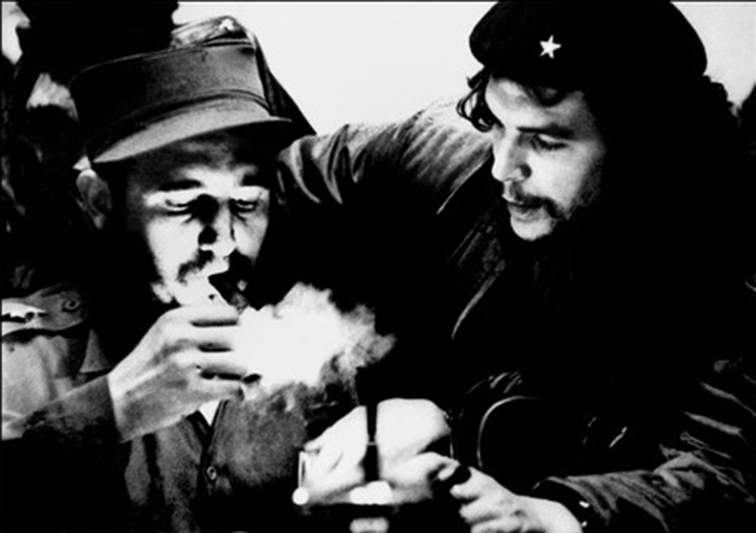(FILES) This file photo taken in the 1960s shows then Cuban Prime Minister Fidel Castro (L) lighting a cigar while listens Argentine Ernesto Che Guevara