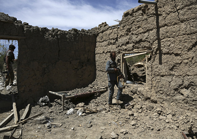 Afghan security police stand guard at the destroyed house after an operation in Asad Khil near the site of a U.S. bombing in the Achin district of Jalalabad, east of Kabul, Afghanistan
