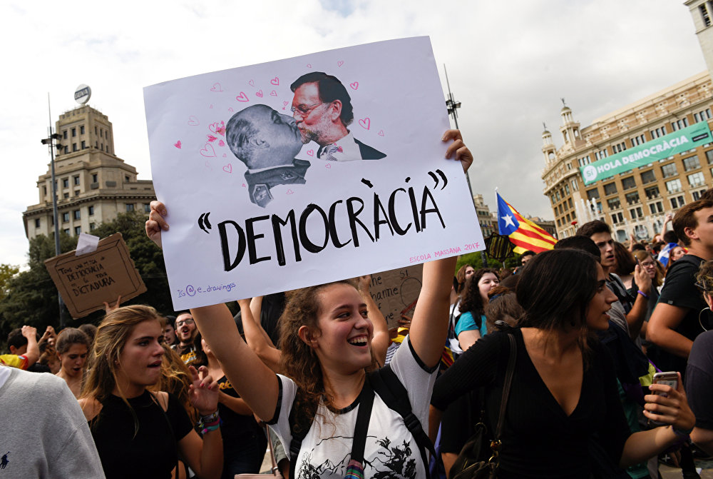 A woman holds up a banner reading Democracy depicting former Spanish dictator Francisco Franco kissing Spanish Prime Miniser Mariano Rajoy during a protest one day after the banned independence referendum in Barcelona, Spain, October 2, 2017.