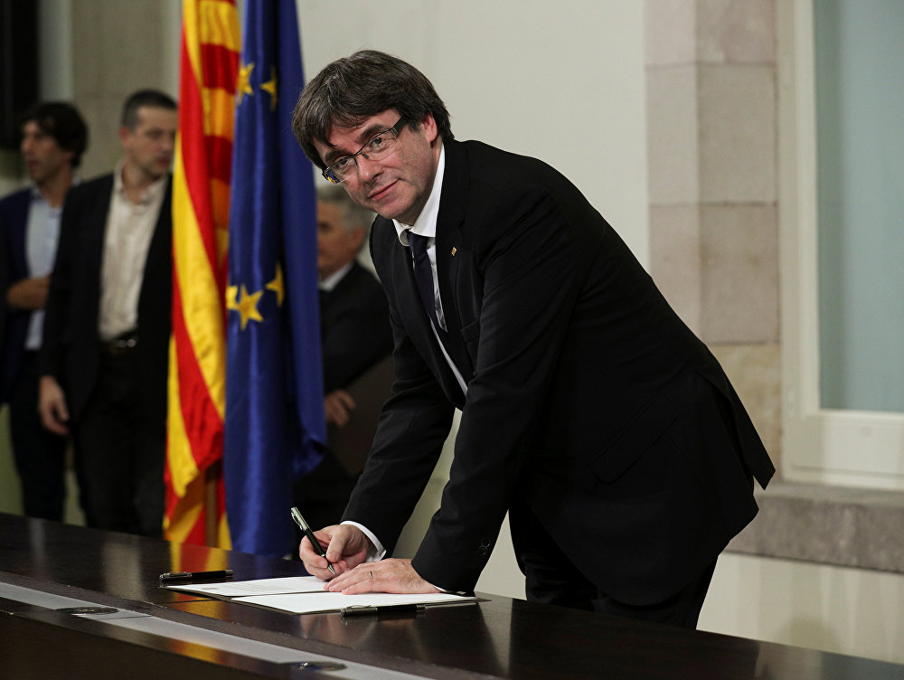 Catalan President Carles Puigdemont signs a declaration of independence at the Catalan regional parliament in Barcelona, Spain, October 10, 2017.