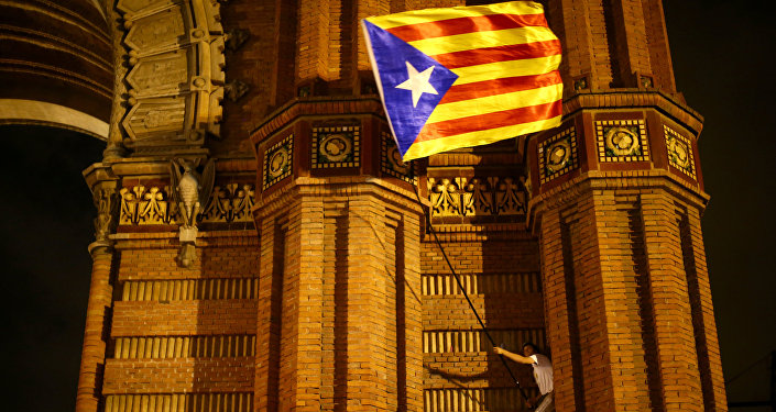 A man waves a separatist Catalonian flag at a pro-independence rally in Barcelona, Spain