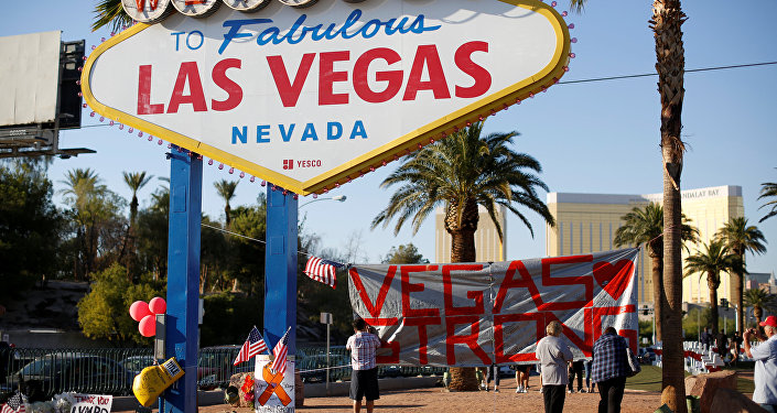 People sign a banner near the Welcome to Fabulous Las Vegas sign following the Route 91 music festival mass shooting in Las Vegas, Nevada, U.S., October 5, 2017