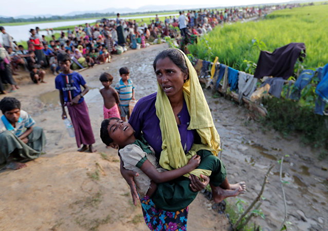 A Rohingya refugee woman who crossed the border from Myanmar a day before, carries her daughter and searches for help as they wait to receive permission from the Bangladeshi army to continue their way to the refugee camps, in Palang Khali, Bangladesh October 17, 2017