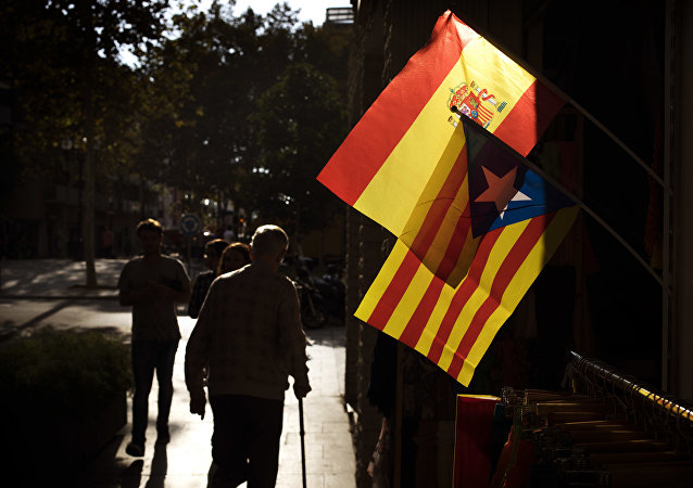 People walk past a Spanish and an estelada, or independence flag, hanging up for sale in a shop in Barcelona, Spain, Wednesday, Oct. 11, 2017
