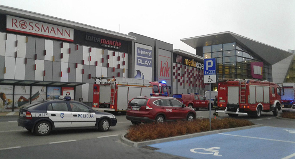 Police and firefighters' cars and trucks stand in front of the VIVO shopping mall where a 27-year-old man attacked people with a knife killing one person and injuring several others in Stalowa Wola, southeastern Poland