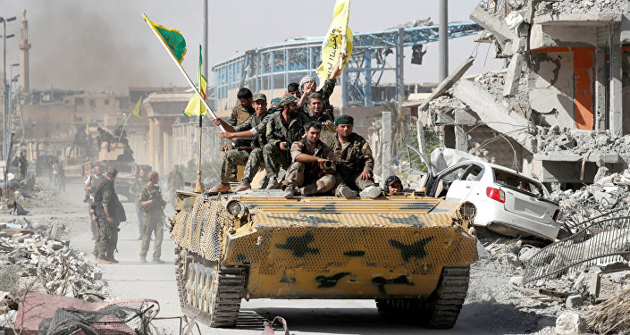 Syrian Democratic Forces (SDF) fighters ride atop of military vehicle as they celebrate victory in Raqqa, Syria, October 17, 2017