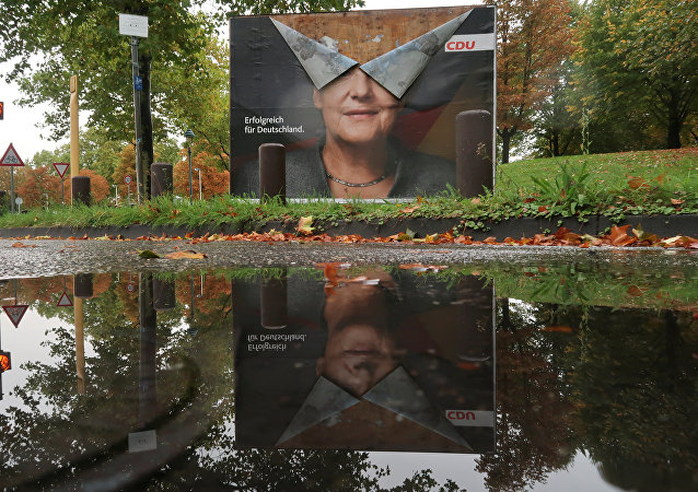 An election campaign poster of Angela Merkel, German Chancellor and leader of the Christian Democratic Union party CDU is reflected in a puddle one week following Germany's general election in Bonn, September 30, 2017