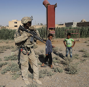 A U.S. soldier stands near Syrian children on a road that links to Raqqa, Syria, Wednesday, July 26, 2017