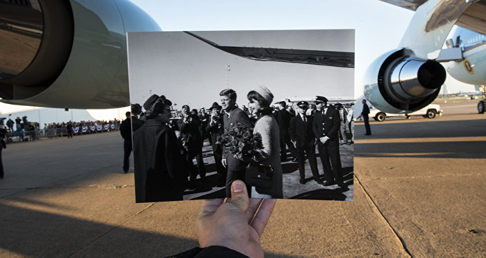 This file photo taken on November 8, 2013 shows a historic photo dated November 22, 1963 showing former US President John F. Kennedy and First Lady Jacqueline Kennedy arriving in Dallas, Texas (Cecil Stoughton, White House Photographs, John F. Kennedy Presidential Library and Museum, Boston) being held up by the photographer against Air Force One in the background as former US President Barack Obama arrives at Love Field in Dallas, Texas