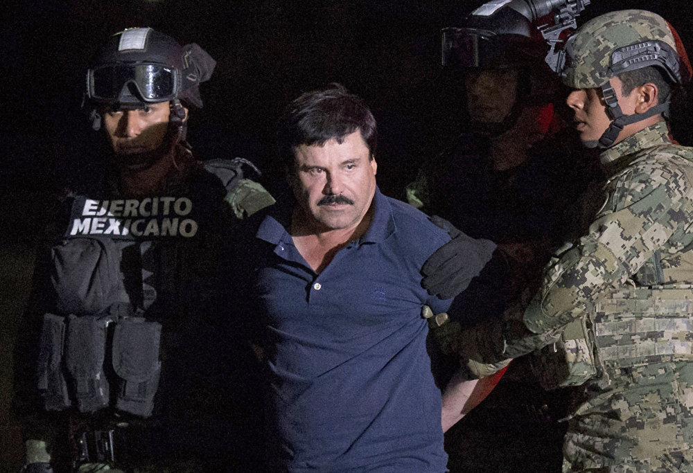 Mexican drug lord Joaquin El Chapo Guzman is escorted by army soldiers to a waiting helicopter, at a federal hangar in Mexico City, Friday, Jan. 8, 2016.