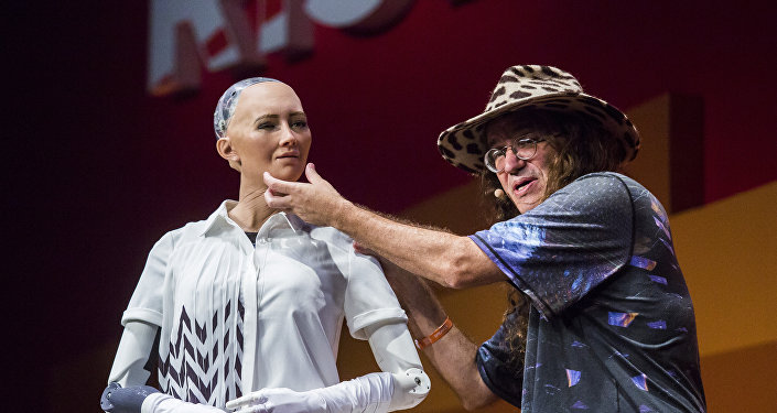 Chief scientist of Hanson Robotics, Ben Goertzel (R), describes to the audience what Sophia the Robot (L) is made of during a discussion about the future of humanity in a demonstration of artificial intelligence (AI) by Hanson Robotics at the RISE Technology Conference in Hong Kong on July 12, 2017