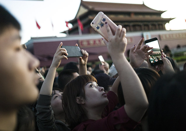 A Chinese lady takes pictures with her phone of the paramilitary guards on Tiananmen square during the rising flag in Beijing on September 20, 2017
