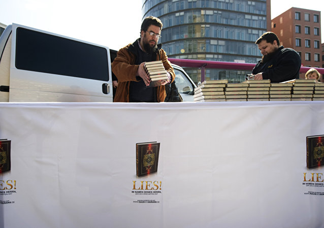 Supporters of the Salafist group House of the Quran (Haus vom Karan) give out Korans at Potsdamer Plarz in Berlin on April 14, 2012. The banner reads: Read! in the name of your Lord