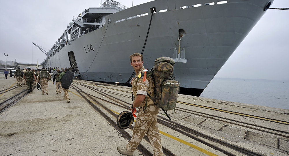 A British soldier looks back while walking to the HMS Albion warship of the British Royal Navy at anchor at port of Santander northern Spain, Tuesday, April 20, 2010.