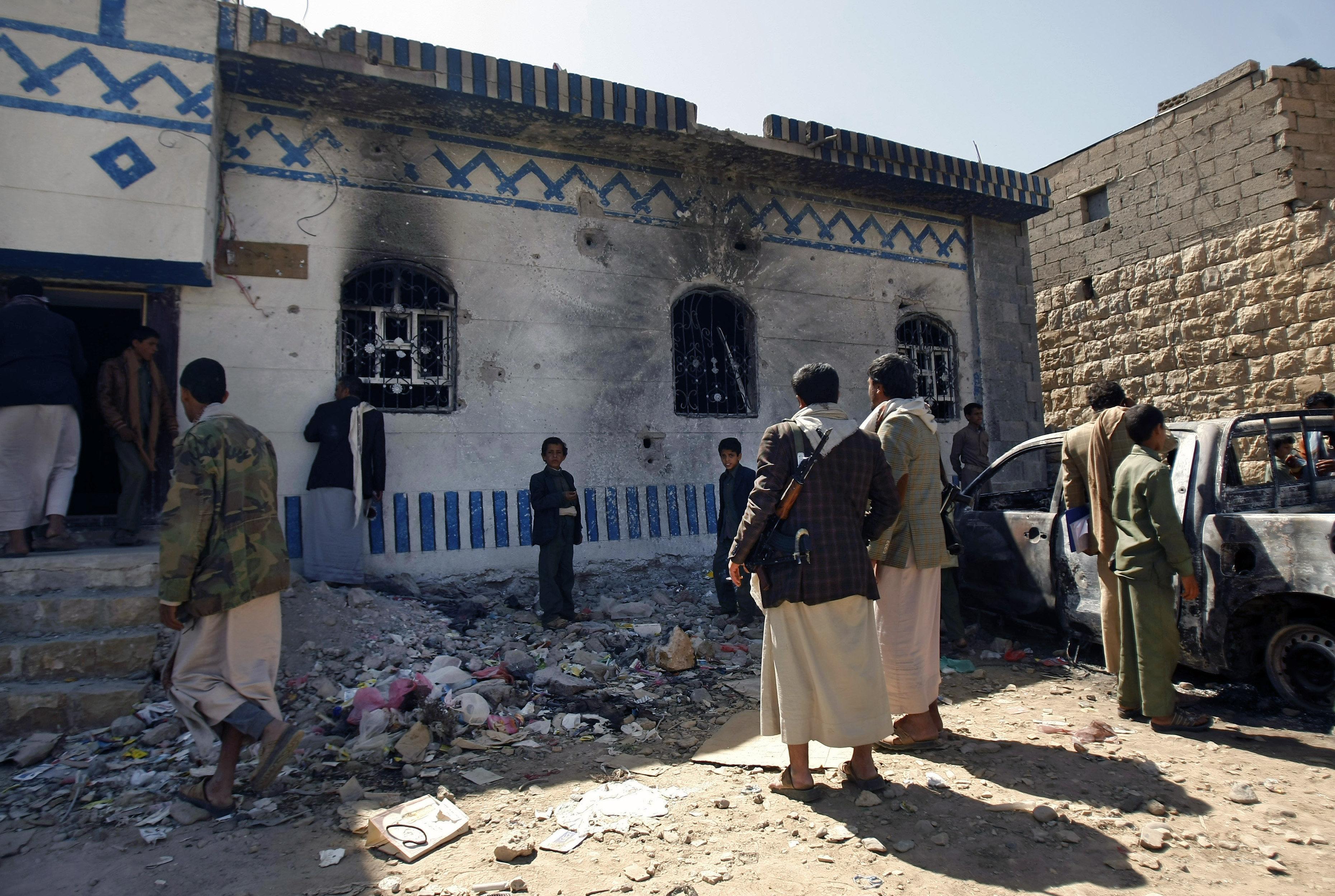Yemenis look at a building damaged during a police raid on a hideout of al-Qaida militants in Arhab region, north of Sanaa, Yemen. (File)