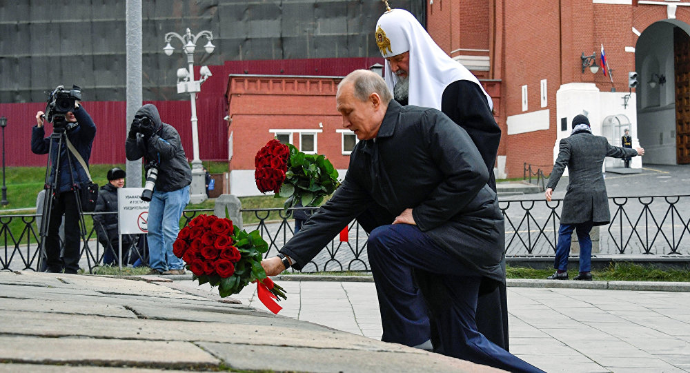 Russian President Vladimir Putin, foreground, and Russian Orthodox Church Patriarch Kirill lay flowers at the monument of Minin and Pozharsky at Red Square in Moscow, during National Unity Day in Moscow, Russia, Saturday, Nov. 4, 2017
