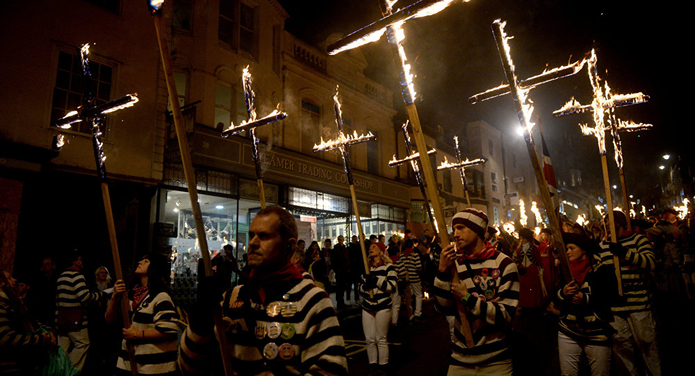 Participants in costumes hold burning crosses as they take part in one of a series of processions during Bonfire Night celebrations in Lewes, Britain November 4, 2017