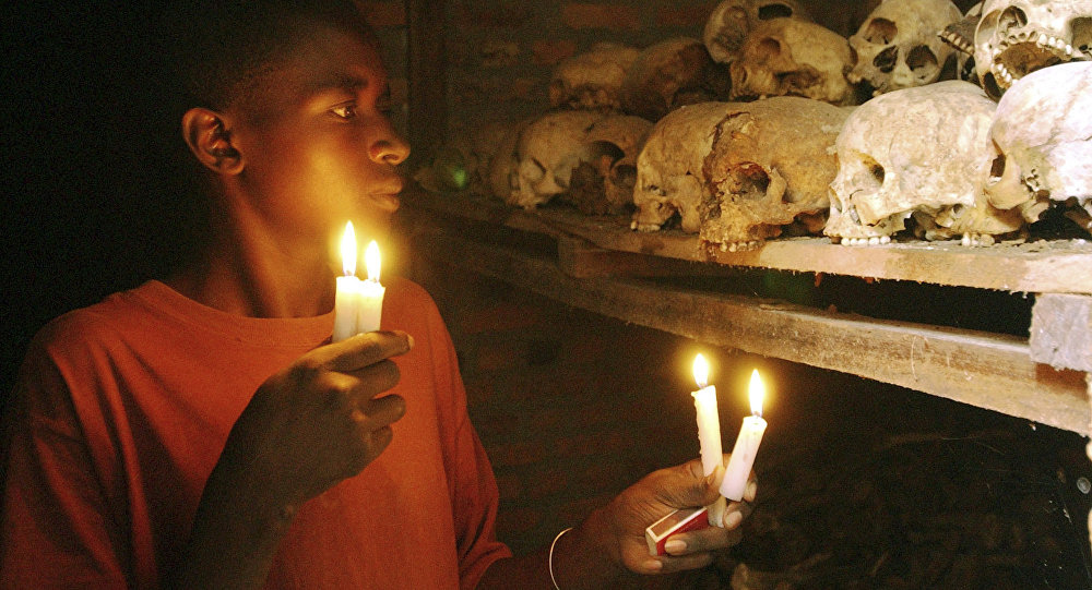 FILE - In this April 6, 2004 file photo, Apollan Odetta, a survivor from the 1994 Rwandan Genocide light candles at a mass grave in Nyamata, Rwanda