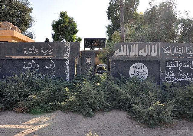 A picture taken on October 20, 2017, shows Islamic State group writting on a wall in the recently seized strategic Syrian town of Mayadeen