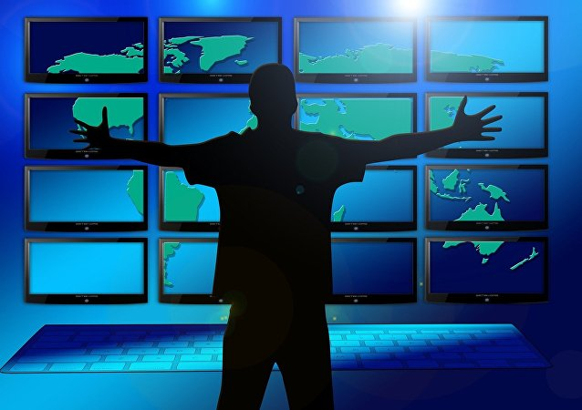 A silhouette of a man in front of multiple screens
