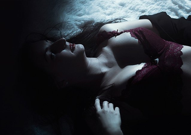A half naked woman lies on the bed in the dark