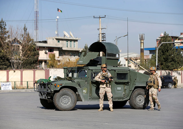 Afghan security forces keep watch at the site of an attack in Kabul, Afghanistan