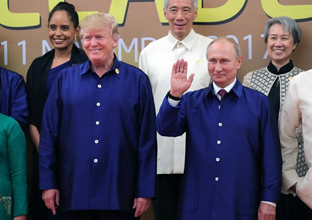 Russian President Vladimir Putin and US President Donald Trump, left, front, taking part in the traditional ceremony of taking photos in national Vietnamese clothes during APEC Economic Leaders' Meeting in Vietnam