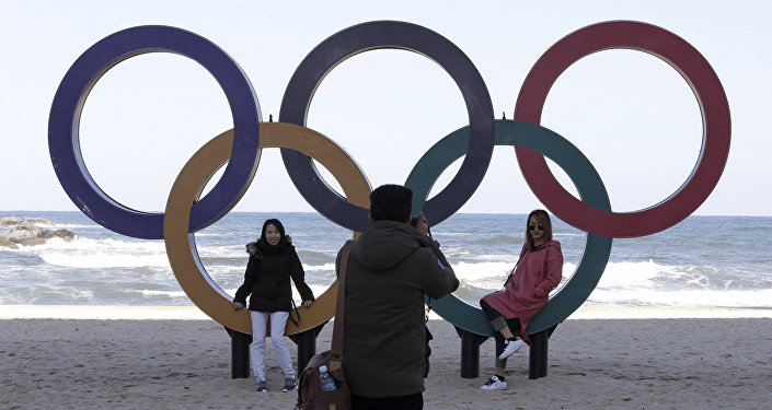 This Oct. 30, 2017, photo show visitors posing with the Olympic Rings at the Gyeongpodae beach, in Gangneung, South Korea