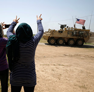People gesture at a US military vehicle travelling in Amuda province, northern Syria April 29, 2017.