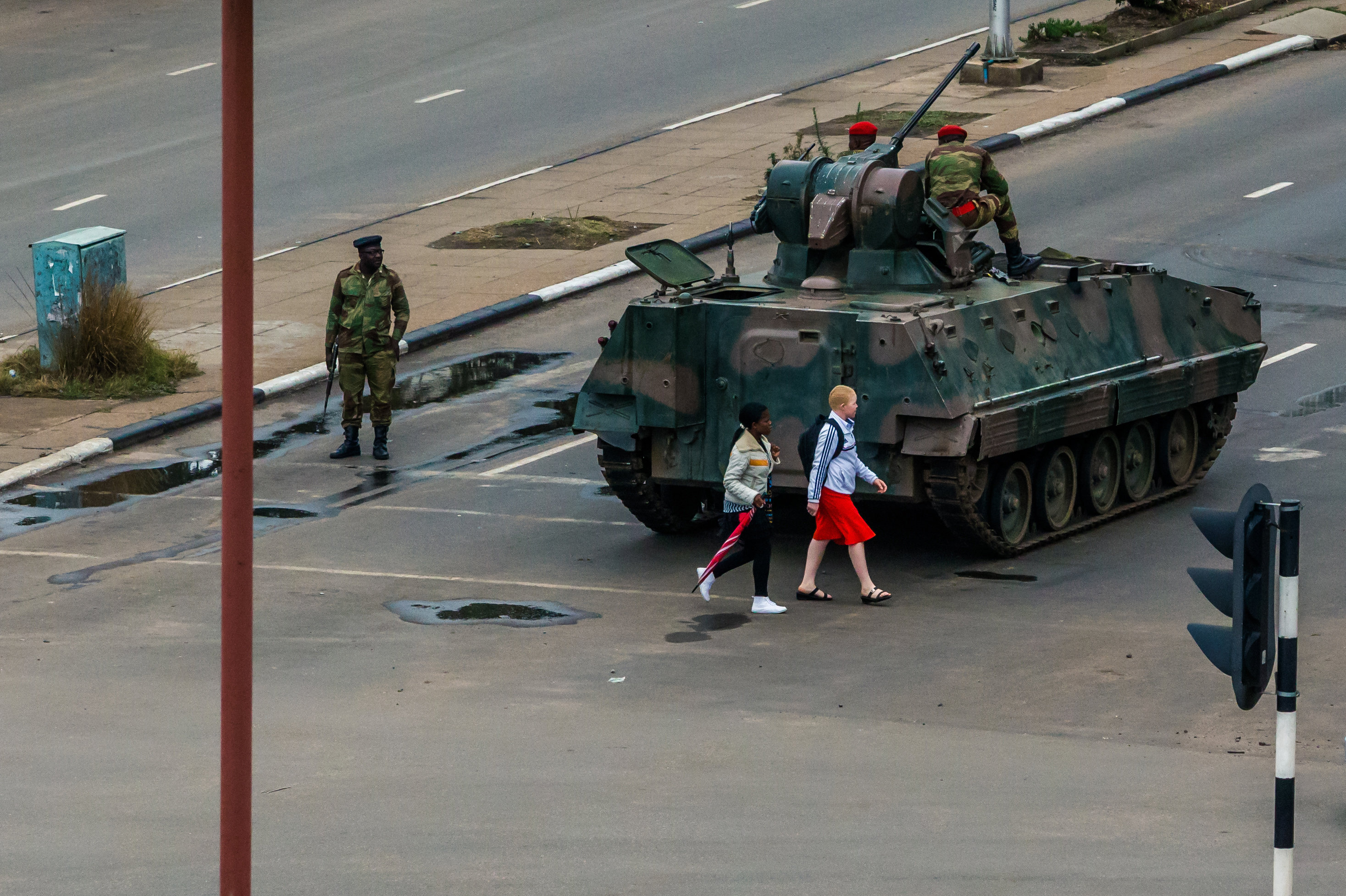 Young women walk past an armoured personnel carrier that stations by an intersection as Zimbabwean soldiers regulate traffic in Harare on November 15, 2017