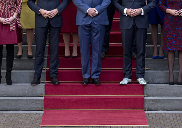 The shoes of Dutch Vice Prime Minister Hugo de Jonge, second right, stand out as he poses with King Willem-Alexander, center, and Dutch Prime Minister Mark Rutte, second left, and other ministers for the official photo of the new Dutch government on the steps of Royal Palace Noordeinde in The Hague, Netherlands, Thursday, Oct. 26, 2017.