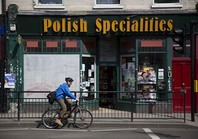 A man as he cycles past a Polish Specialties shop in London.