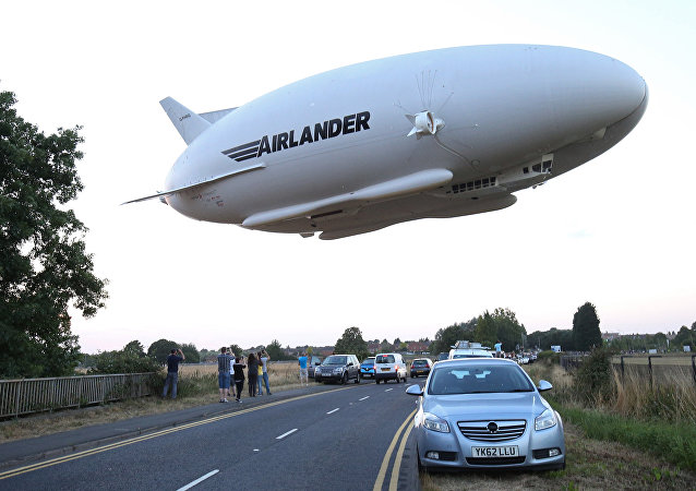 The Hybrid Air Vehicles HAV 304 Airlander 10 hybrid airship is seen in the air over a road on its maiden flight from Cardington Airfield near Bedford, north of London, on August 17, 2016