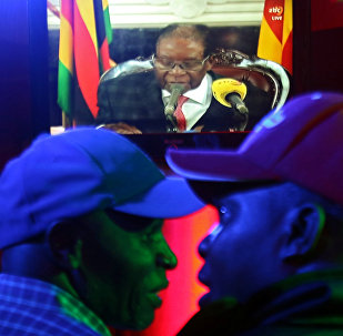 People watch as Zimbabwean President Robert Mugabe addresses the nation on television, at a bar in Harare, Zimbabwe, November 19, 2017
