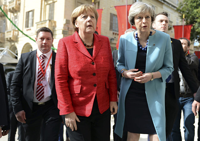 German Chancellor Angela Merkel, left, speaks with British Prime Minister Theresa May, right, as they walk with other EU leaders during an event at an EU summit in Valletta, Malta, on Friday, Feb. 3, 2017.