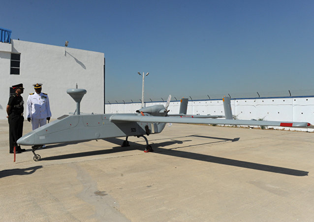 Indian military officers interact next to a Searcher MK II unmanned aerial vehicle (UAV) at the Porbandar airfield in Porbandar, some 400 kms from Ahmedabad, on January 17, 2011