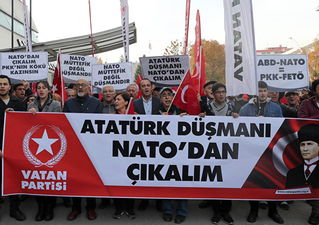 Protestors wave flags and carry a banner during a demonstration against NATO military exercises on November 18, 2017 in Ankara