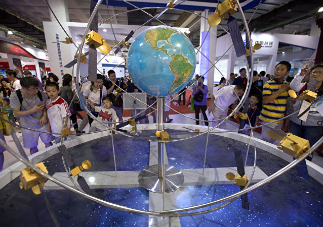 Visitors look at a mockup of China's homegrown Beidou satellite navigation system at the China Beijing International High-Tech Expo in Beijing, Saturday, June 10, 2017