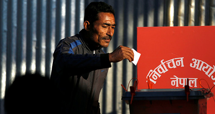 A man cast his vote on a ballot box during the parliamentary and provincial elections at Chautara in Sindhupalchok District November 26, 2017