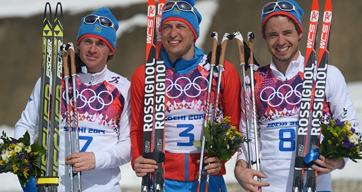 Medalists in the mass start race in men's cross country skiing at the XXII Olympic Winter Games in Sochi during the flower ceremony, from left: silver medalist Maxim Vylegzhanin (Russia); gold medalist Alexander Legkov (Russia); bronze medalist Ilya Chernousov (Russia). (File)