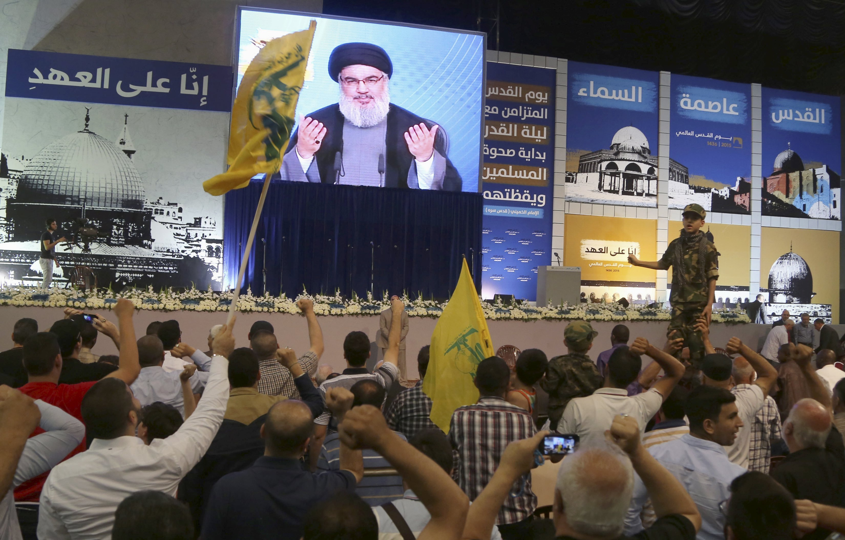 Supporters of Lebanon's Hezbollah leader Sayyed Hassan Nasrallah gesture as he appears on a screen during a rally to mark Quds (Jerusalem) Day in Beirut's southern suburbs July 10, 2015.