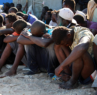 Illegal migrants from sub-Saharan Africa rest after they were rescued by the Libyan coast guard when their boat sank off the coastal town of Guarabouli, 60 km (36 miles) east of the capital Tripoli on October 2, 2014