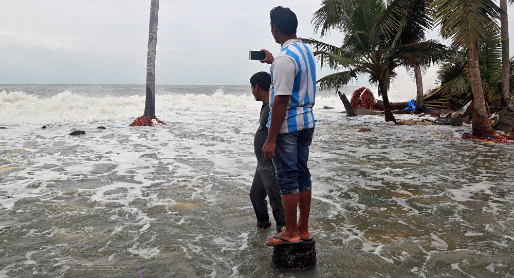 A man uses his mobile phone to take photographs of tides on the shores of the Arabian Sea, after flooding caused by Cyclone Ockhi in the coastal village of Chellanam in the southern state of Kerala, India, December 2, 2017