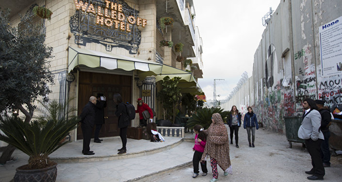 People pass by the The Walled Off Hotel and the Israeli security barrier in the West Bank city of Bethlehem