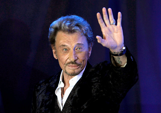 French singer Johnny Hallyday waves to fans attending a ceremony to promote his new album Jamais seul (Never alone) at the Virgin Megastore in Paris early March 28, 2011