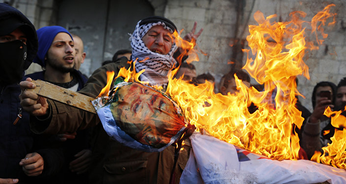 Palestinian protestors burn an effigy of US President Donald Trump following his decision to recognise Jerusalem as the capital of Israel, in the West Bank city of Nablus, on December 7, 2017