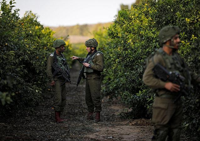 Israeli soldiers patrol the area near the Israeli Gaza border on its Israeli side