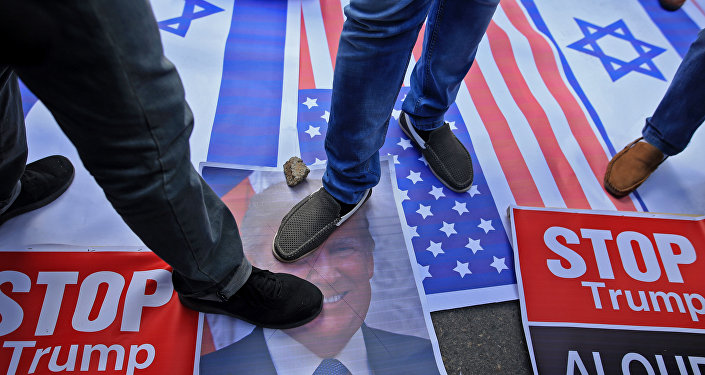 Palestinian protesters step on US and Israeli flags and on a portrait of US President Donald Trump following his decision to recognise Jerusalem as the capital of Israel in Gaza City