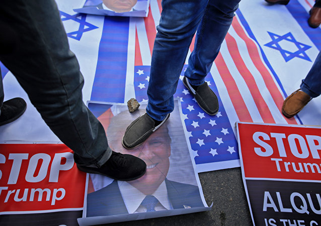 Palestinian protesters step on US and Israeli flags and on a portrait of US President Donald Trump following his decision to recognise Jerusalem as the capital of Israel, in Gaza City
